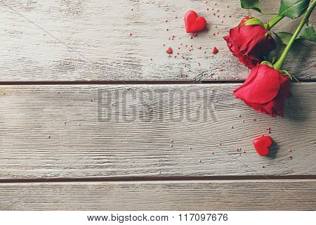 Beautiful roses with small hearts on wooden background