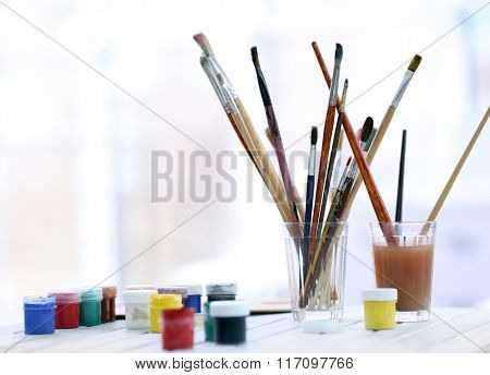 Drawing set with brushes and paints on white table