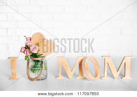 I love mom inscription of wooden letters with heart and flowers on white brick wall background