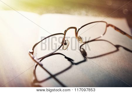 Opened book and eyeglasses on it, close up