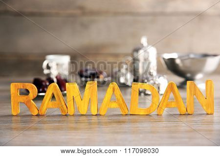 Ramadan word with wooden letters and on table, close up