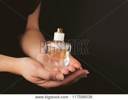 Young woman holding bottle perfume on dark background