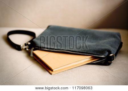 Fashion female handbag with book on a sofa, close up