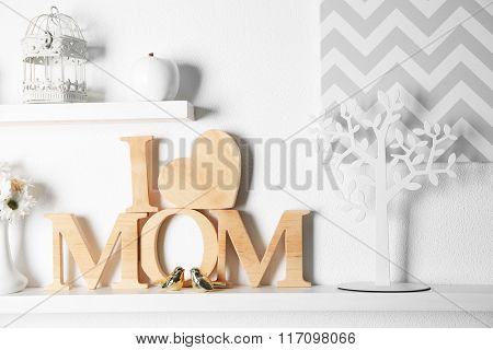 I love mom inscription of wooden letters with heart and flowers on white wall background