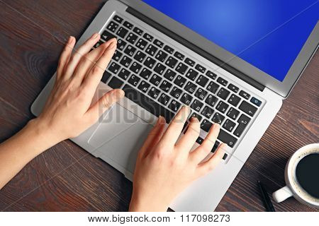 Coffee cup and female hands using laptop, on the wooden background, close-up