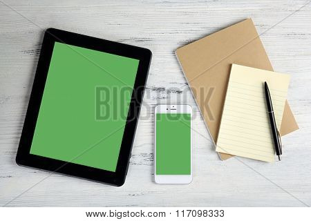 Modern mobile phone, tablet and notebook on white wooden background