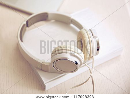 Headphones and book on white table, closeup