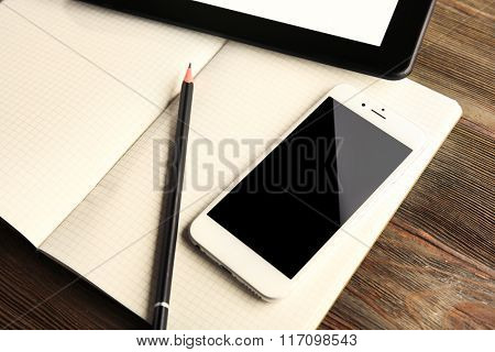 Mobile phone, notebook, pen and tablet on the table, close-up
