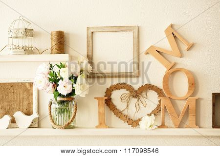 Wooden decor and flowers for mother's day on a shelf