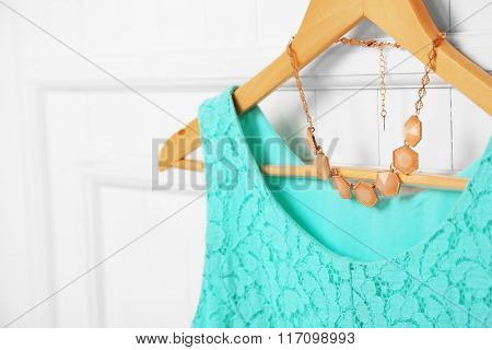 Blouse and necklace on hanger on wall background