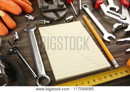 Different kinds of tools with a notebook on wooden background