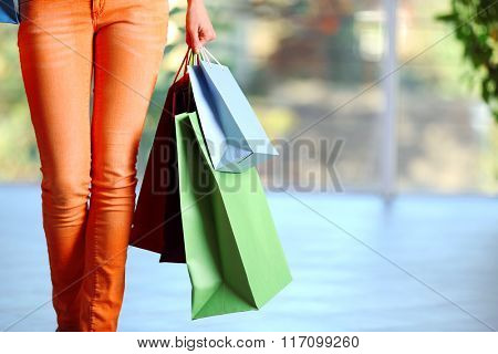 Young  woman with shopping packages on defocused background