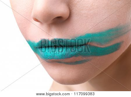 Woman's face with smeared blue lipstick isolated on white, close up