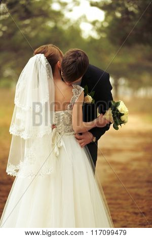 Groom kissing bride on a forest background
