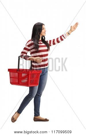 Full length portrait of a young woman holding a shopping basket and reaching for something isolated on white background