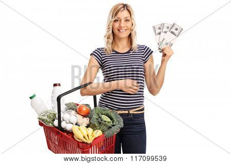 Young woman holding a shopping basket with groceries and a few stacks of money isolated on white background