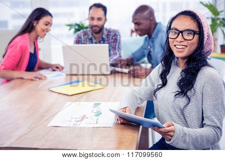 Portrait of cheerful businesswoman holding digital tablet while sitting with colleagues in office