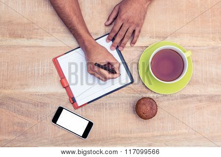 Overhead view of person writing on diary at table