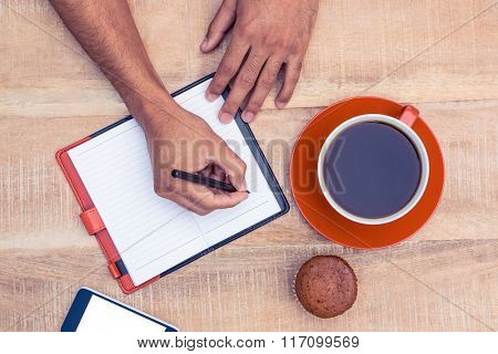 Man writing on diary at table by coffee and cup cake