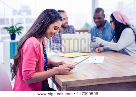 Happy young businesswoman using digital tablet at office
