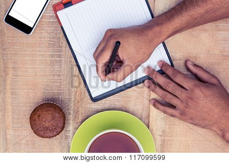 Cropped image of man writing on diary at table by coffee and cup cake