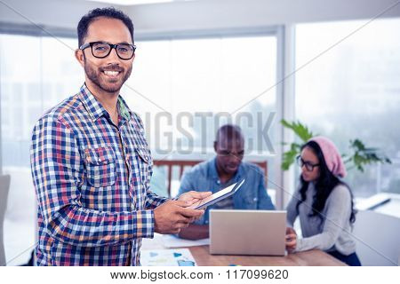 Portrait of happy businesswomen using digital tablet while standing at office