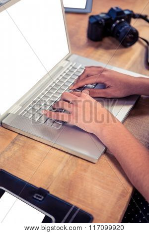 Businesswoman typing on laptop keyboard at creative office