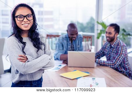 Portrait of happy businesswoman standing with arms crossed with colleagues seen in background