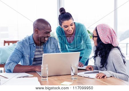 Young business people discussing over laptop in creative office