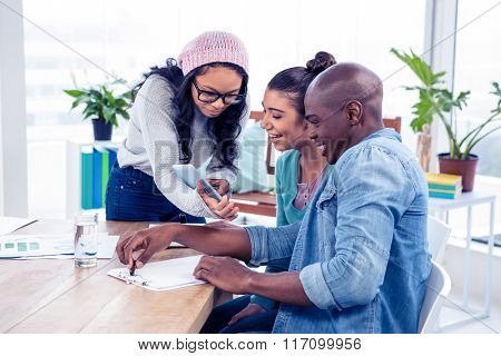 Businesswoman discussing with colleagues over digital tablet in creative office