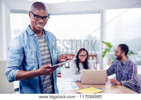 Portrait of happy young businessman using digital tablet while standing at office