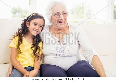 Happy grandmother and granddaughter smiling at home