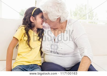 Grandmother and granddaughter looking at each other at home