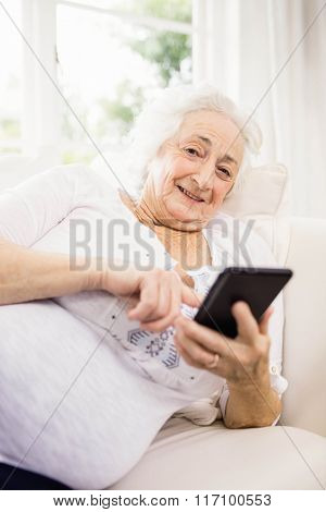 Elderly woman using her smartphone lying on sofa