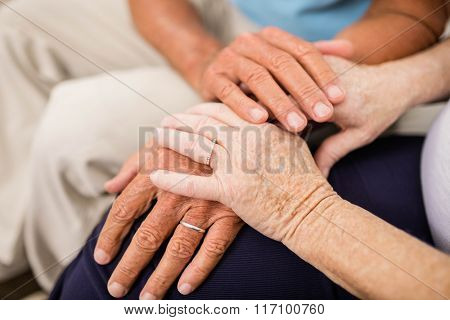 Cute senior couple holding hands on sofa
