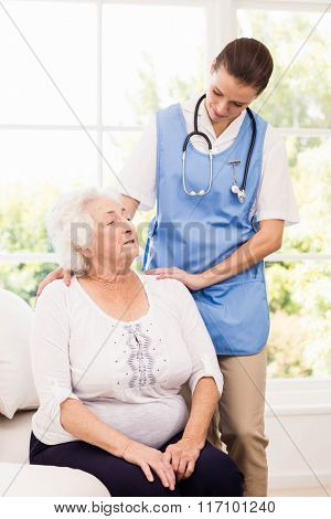 Nurse taking care of sick elderly woman at home