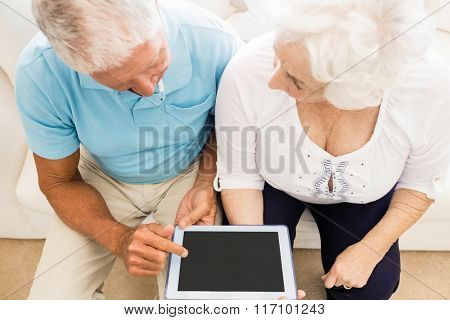 Focused senior couple using tablet at home