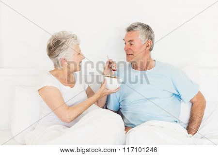 Happy senior woman feeding her husband at bed