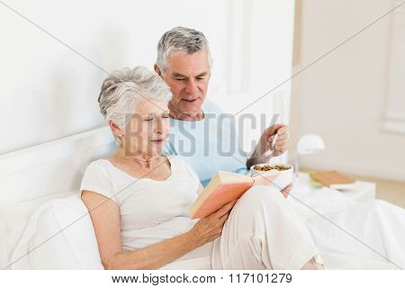 Happy senior couple at bed eating cereals and reading book
