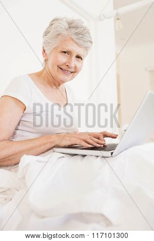 Mature woman using laptop and smiling at the camera sitting on bed