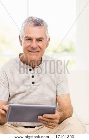 Smiling senior man using tablet on the sofa