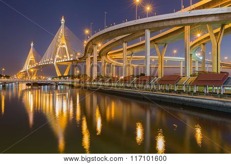 Suspension bridge with highway interchanged at night with water reflection, Bangkok Thailand