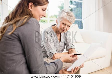 Smiling businesswoman showing documents to senior woman in living room