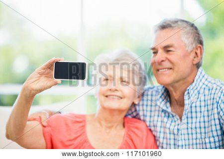 Happy senior couple taking a selfie on the sofa