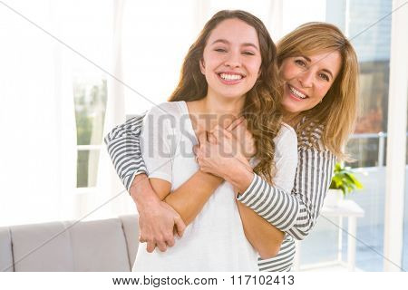 Smiling mother and daughter at home