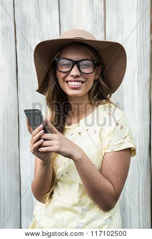 Smiling pretty women with glasses holding mobile phone
