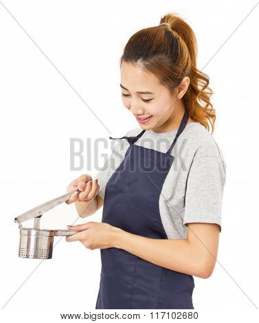 Asian Woman Wearing Apron And Showing The Crushed Potatoes Tool.