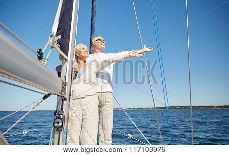 senior couple enjoying freedom on sail boat in sea