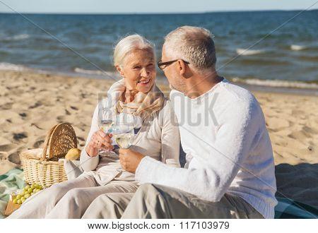 happy senior couple talking on summer beach