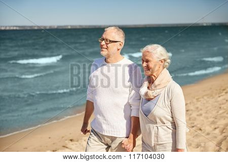 happy senior couple walking along summer beach